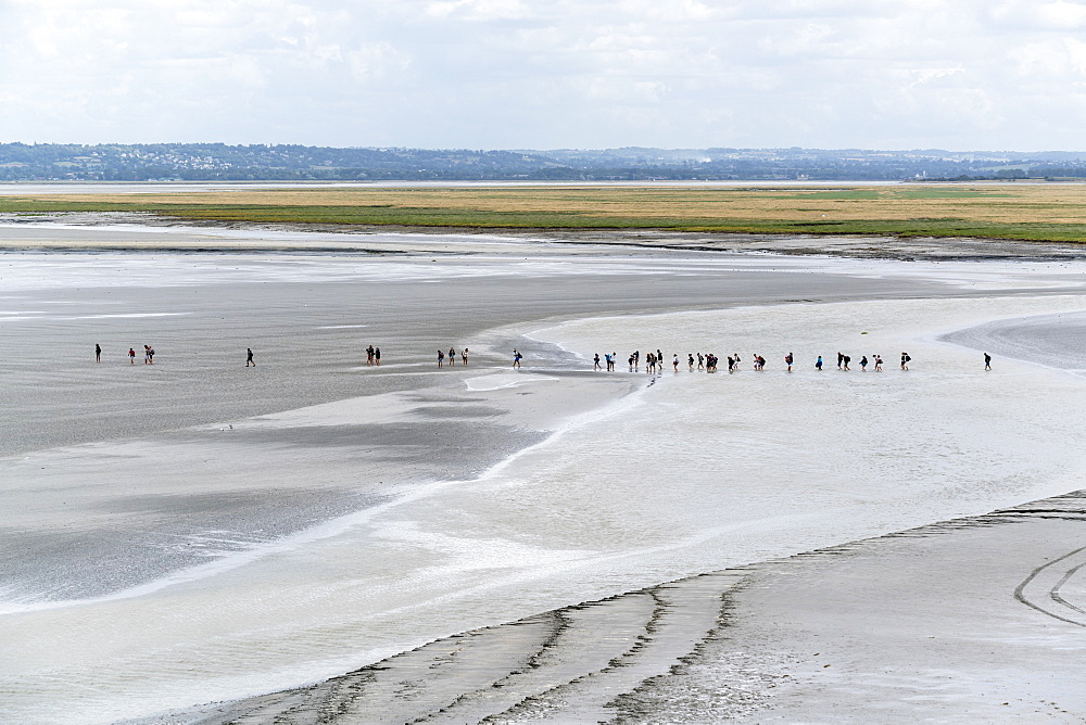 People walking on the sand during low tide. Mont-Saint-Michel, Normandy, France.