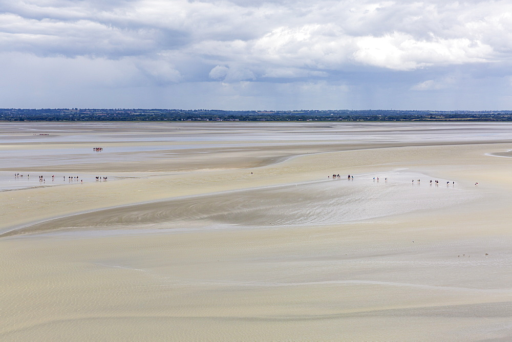 Photo of People walking on the sand during low tide. Mont-Saint-Michel, Normandy, France