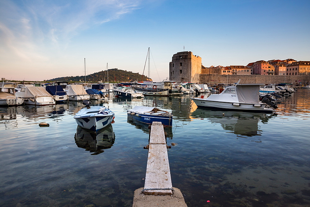 Boats in Dubrovnik harbour during sunset. Croatia.