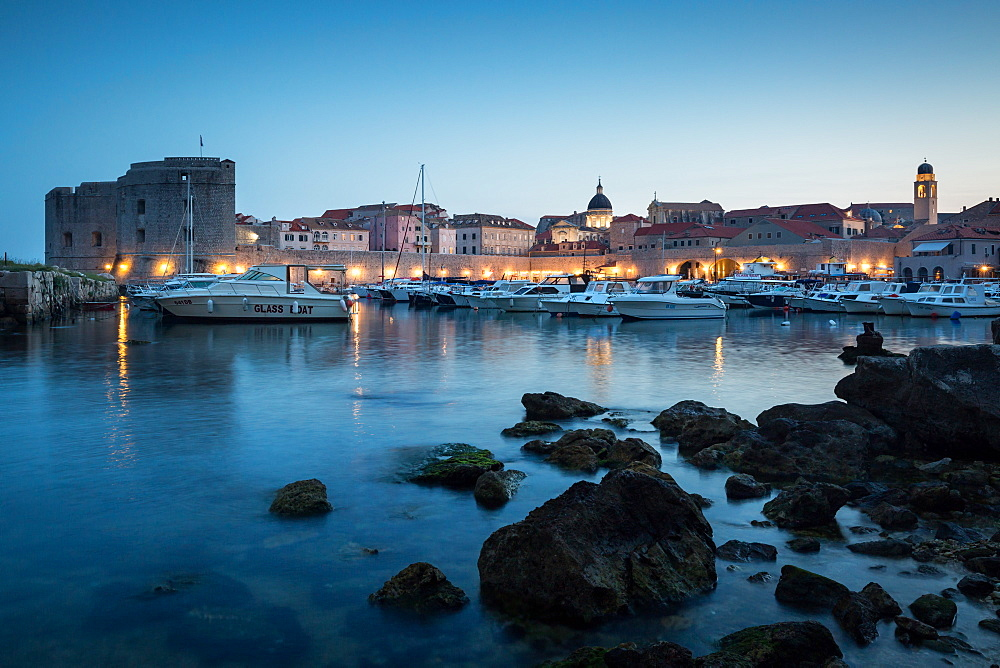 The lights of old town Dubrovnik and its harbour during blue hour. Croatia.