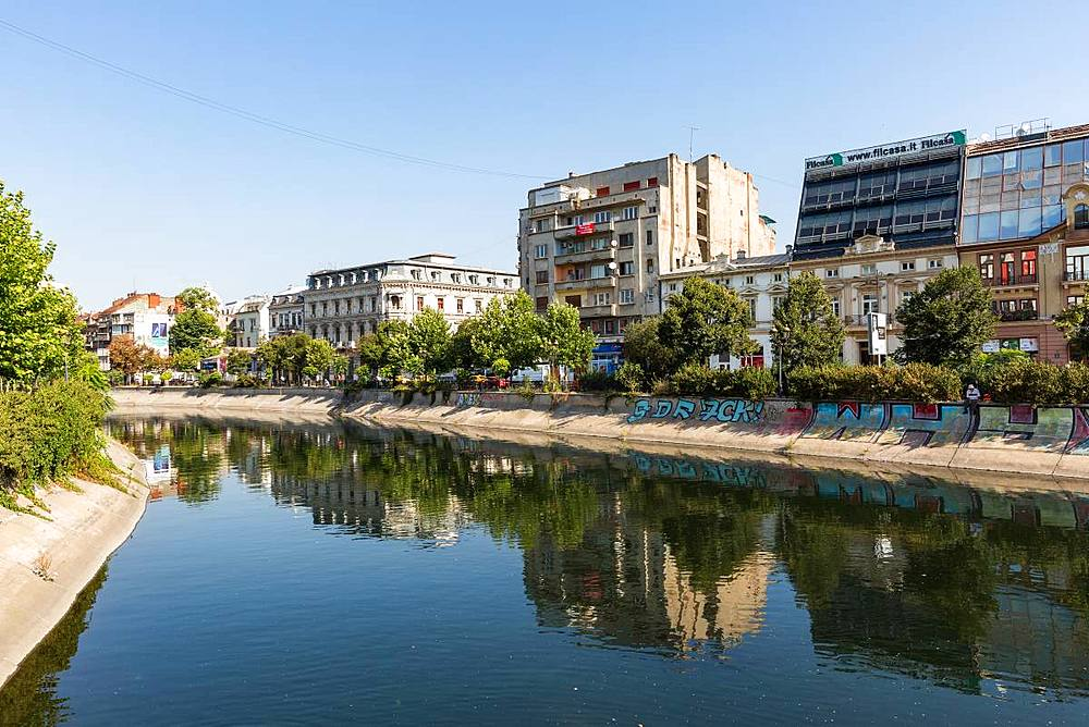 Communist era buildings are reflected in the Dâmbovița River in Bucharest, Romania. - 1263-130