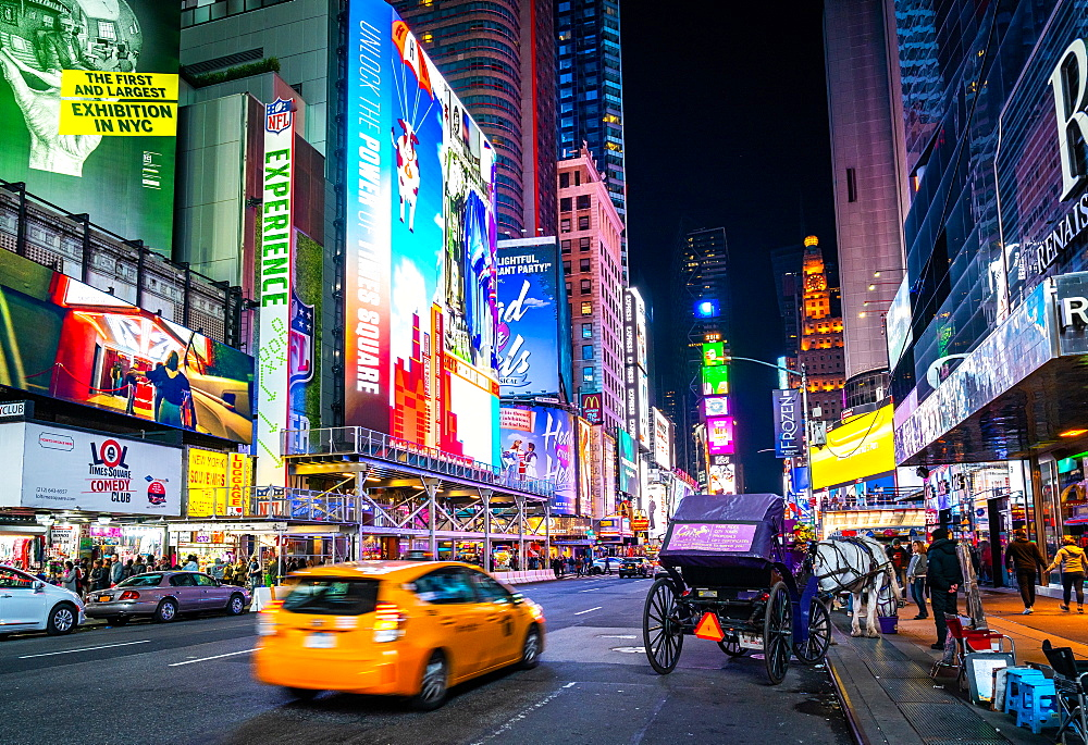 The bright lights of New York City's Times Square with an iconic yellow cab passing through, New York, United States of America, North America - 1263-147