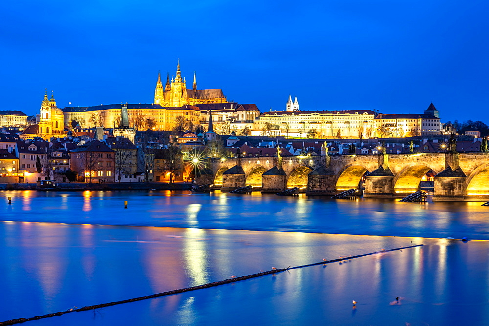 St. Vitus Cathedral and Prague Castle lit up during the evening blue hour reflecting in the Vltava River, UNESCO World Heritage Site, Prague, Czech Republic, Europe