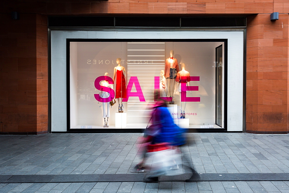 The movement of shoppers at Liverpool One shopping centre in front of a shop with a sale on, Liverpool, Merseyside, England, United Kingdom, Europe
