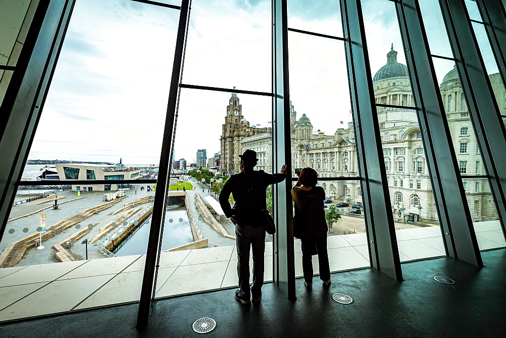 A couple look out over Pier Head and the Liver Building from the large windows at the Museum of Liverpool, Liverpool, Merseyside, England, United Kingdom, Europe