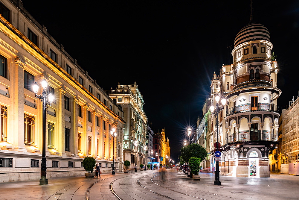 The lights of Seville's buildings at night looking down the Avenida de la Constitucion towards the Catedral de Sevilla, Seville, Andalusia, Spain, Europe