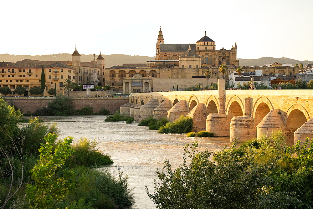 The Roman Bridge (Puente Romano) and The Great Mosque of Cordoba in the glow of sunset at golden hour, UNESCO World Heritage Site, Cordoba, Andalusia, Spain, Europe