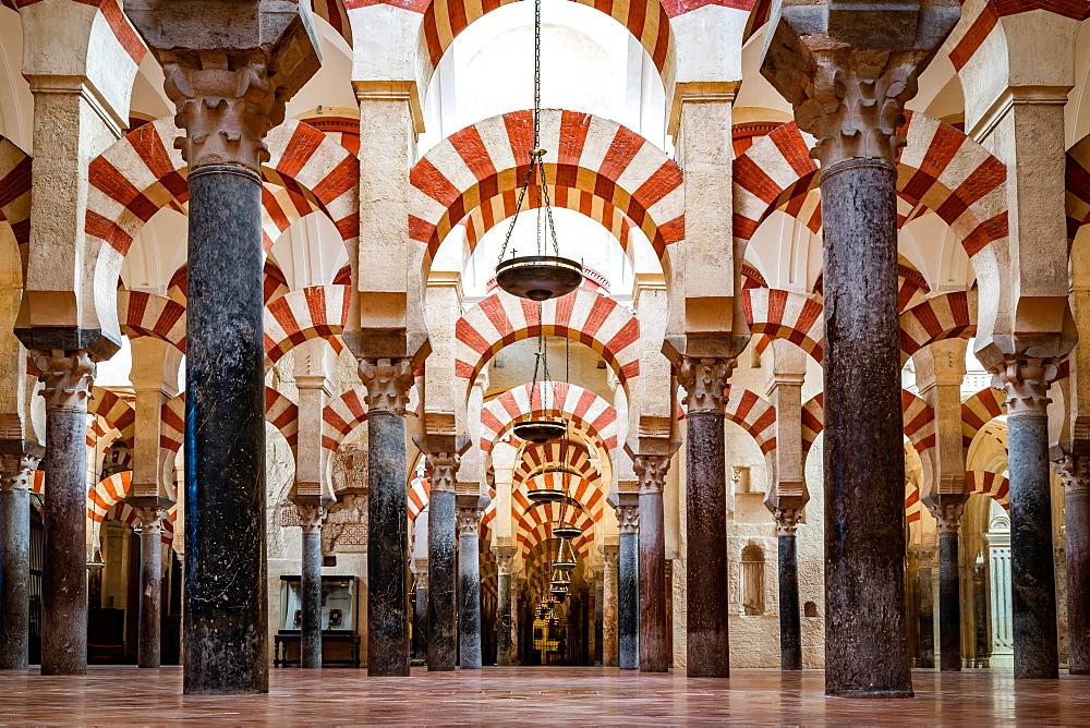 The red and white stone Arches of Mezquita de Cordoba / Cordoba Mosque Cathedral. Cordova, Andalusia, Spain.