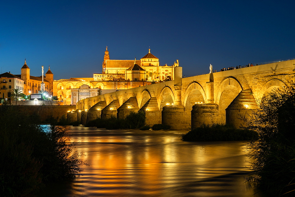 The Roman Bridge (Puente Romano) and The Great Mosque of Cordoba lit up during evening twilight, dusk. Andalusia. Spain