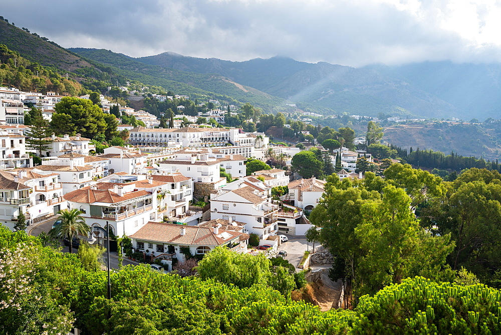 Sun rays burst through the clouds over the white washed buildings of Mijas Pueblo, Andalusia, Spain.