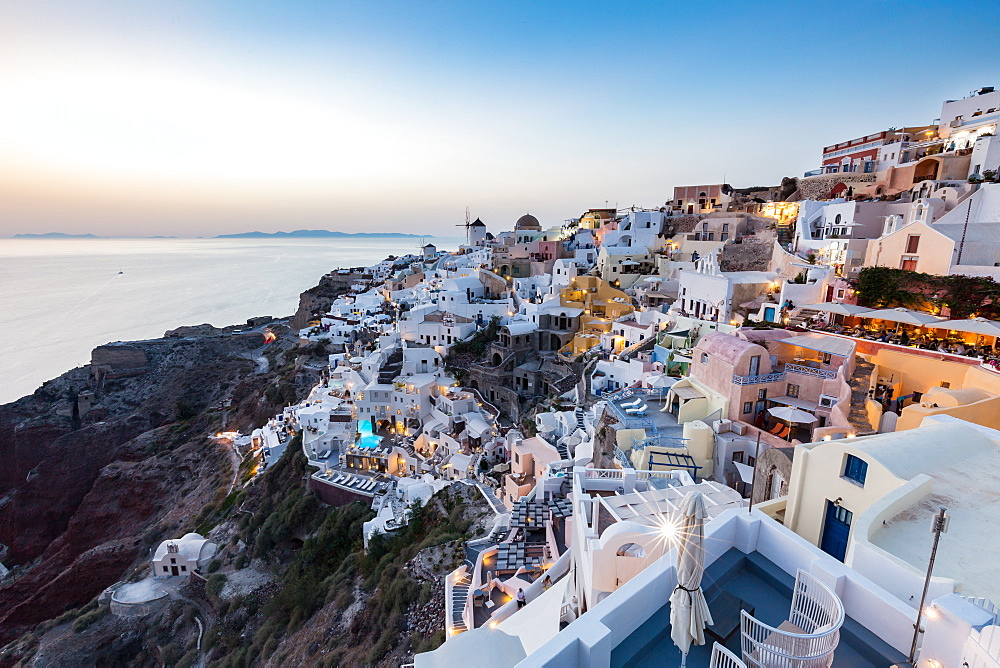 Sunset view over the whitewashed buildings and windmills of Oia, Santorini, Cyclades, Greek Islands, Greece, Europe