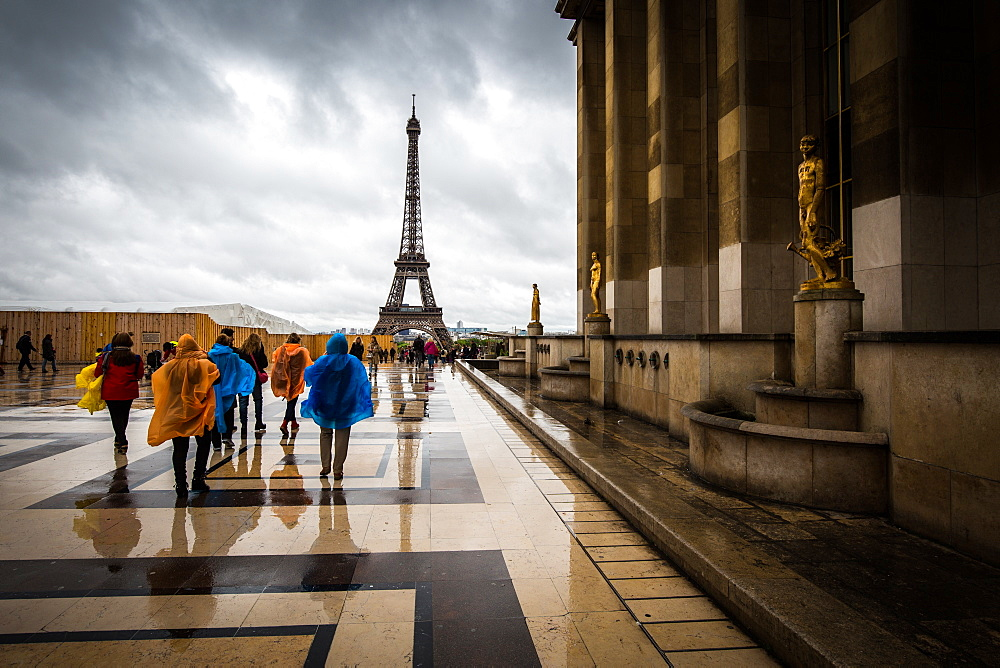 Heading towards the Eiffel Tower, tourists brave the rain in colourful ponchos at the Palais De Chaillot, Paris, France, Europe