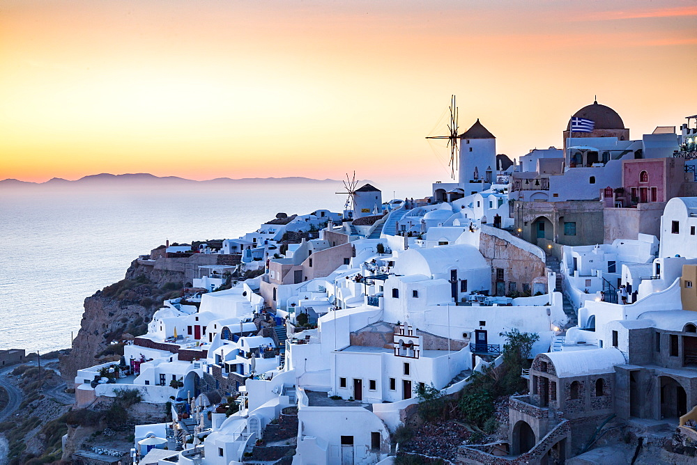 Sunset view over the whitewashed buildings and windmills of Oia from the castle walls, Santorini, Cyclades, Greek Islands, Greece, Europe