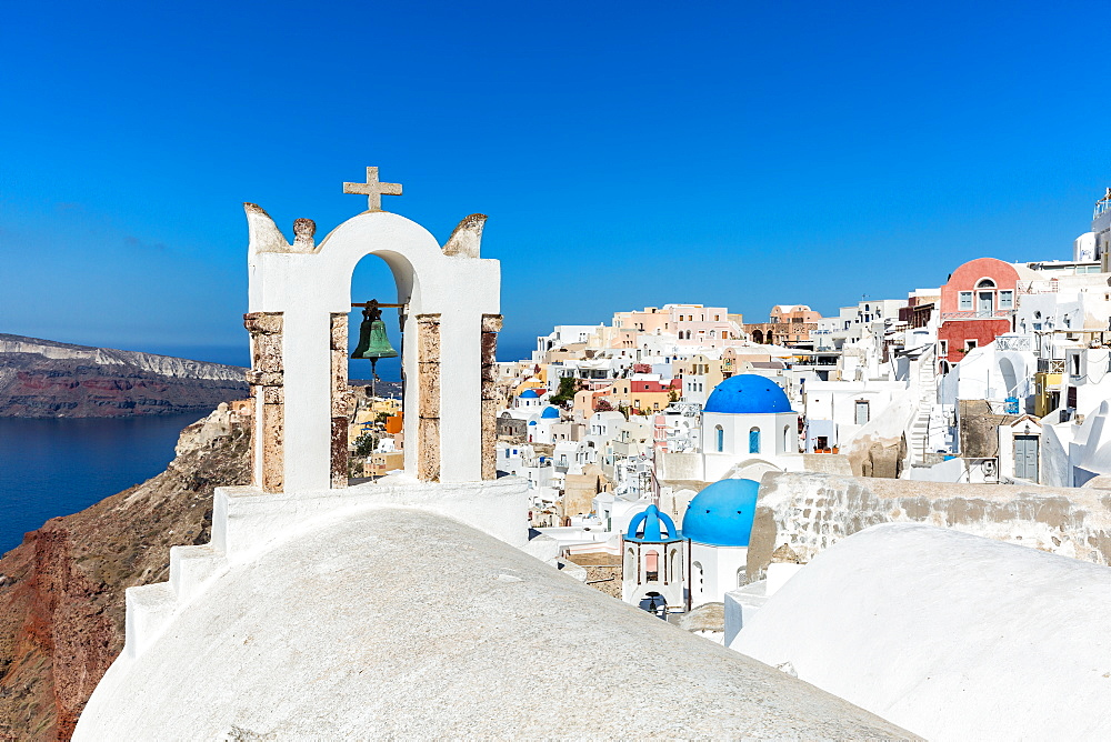 A church roof and bell with the white washed stone walls and blue church cupolas of Oia, Santorini, Cyclades, Greek Islands, Greece, Europe