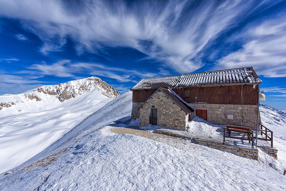 Italy, Abruzzo, Gran Sasso e Monti della Laga, Corno Grande peak and Duca degli Abruzzi mountain hut in Winter