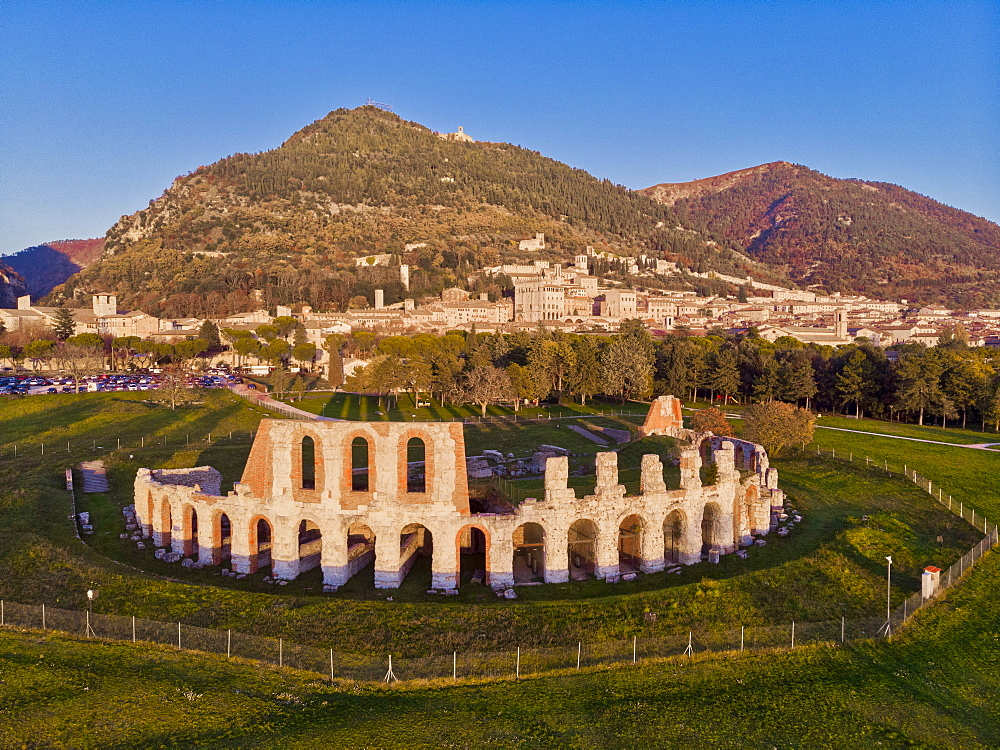 Italy, Umbria, Gubbio, The town and the Roman Theater at sunset (Drone) - 1264-282