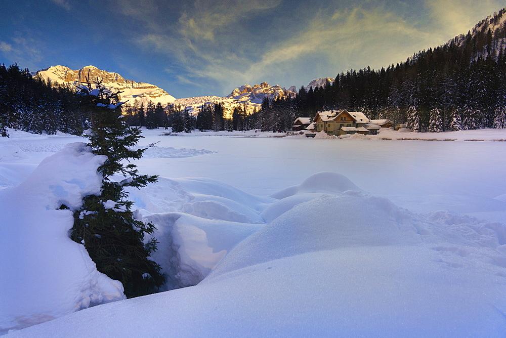 Italy, Dolomites, Trentino, Rendena Valley, Lake Nambino and Brenta mountain range at sunset in Winter