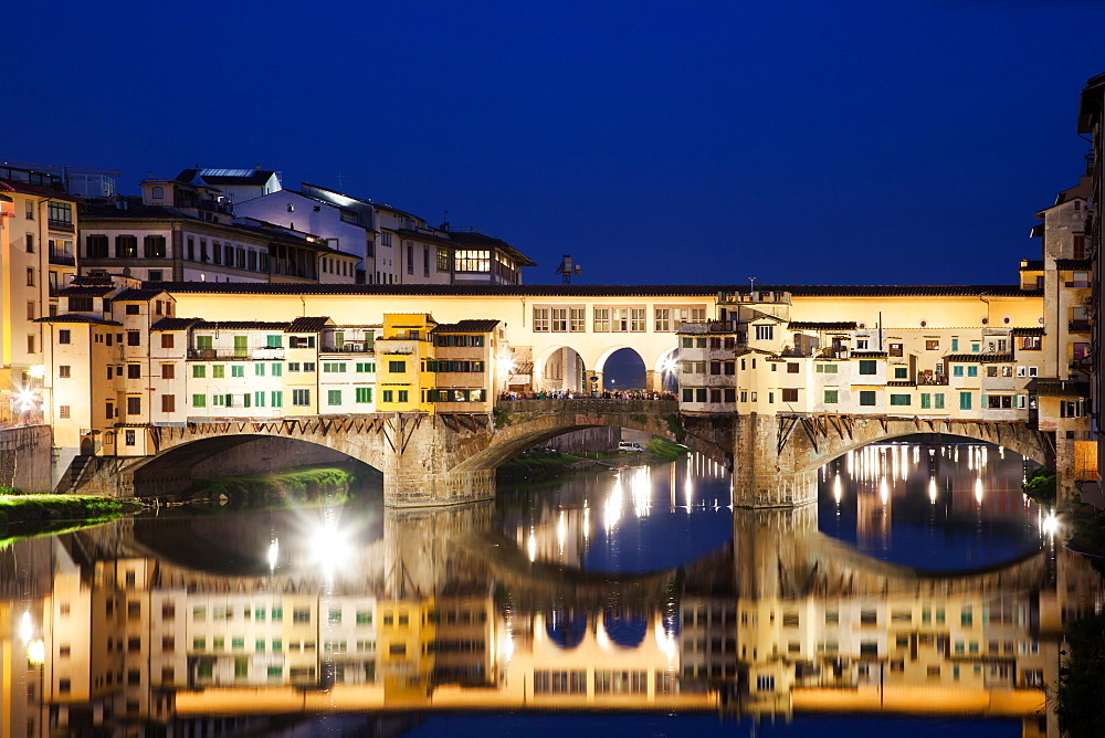 Ponte Vecchio at night reflecting in river Arno, Florence