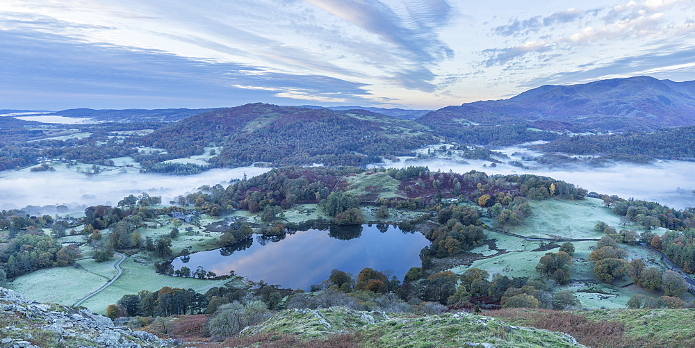 View of Loughrigg Tarn and early morning mists in autumn from Loughrigg Fell, Lake District National Park, UNESCO World Heritage Site, Cumbria, England, United Kingdom, Europe