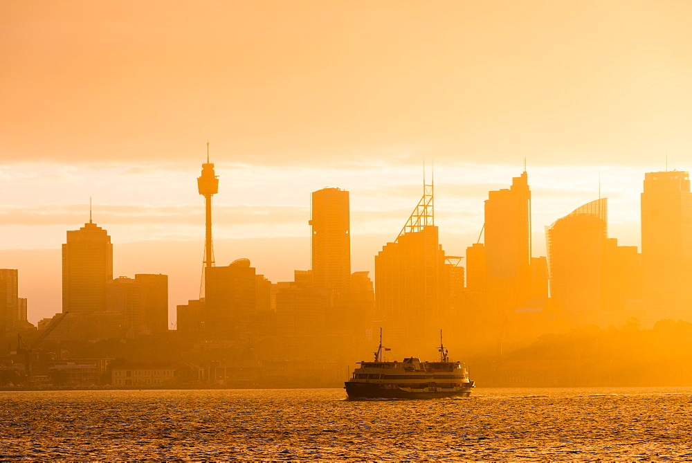 Sydney city skyline looking towards the sun with ferry. New South Wales, Australia.