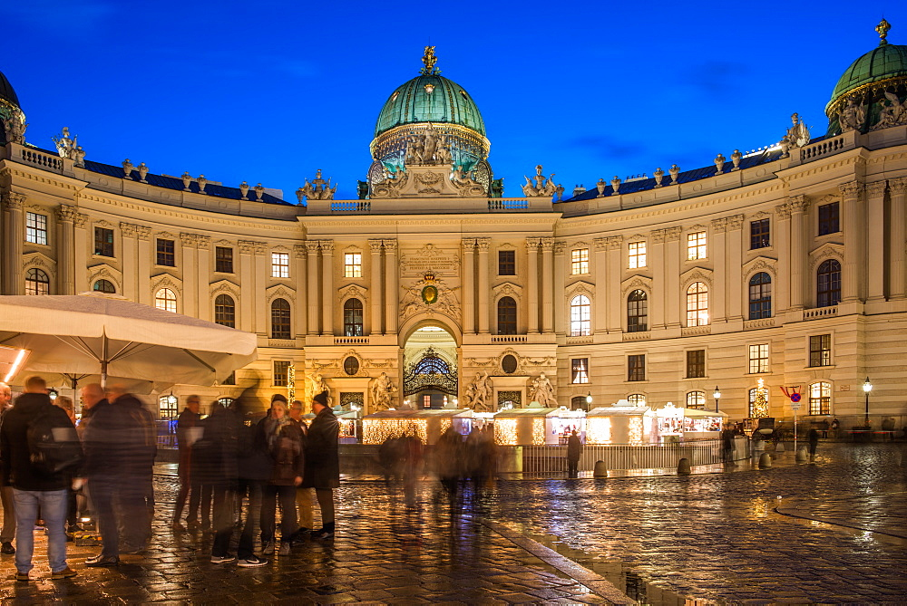 Christmas market on Michaelerplatz with Hofburg palace at dusk. Vienna, Austria.