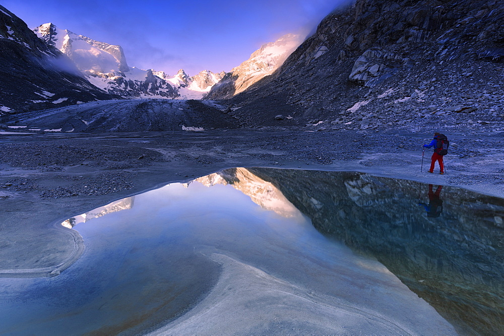 Hiker looks at sunrise from a pond at Forno Glacier, Forno Valley, Maloja Pass, Engadine, Graubunden, Switzerland, Europe - 1269-197