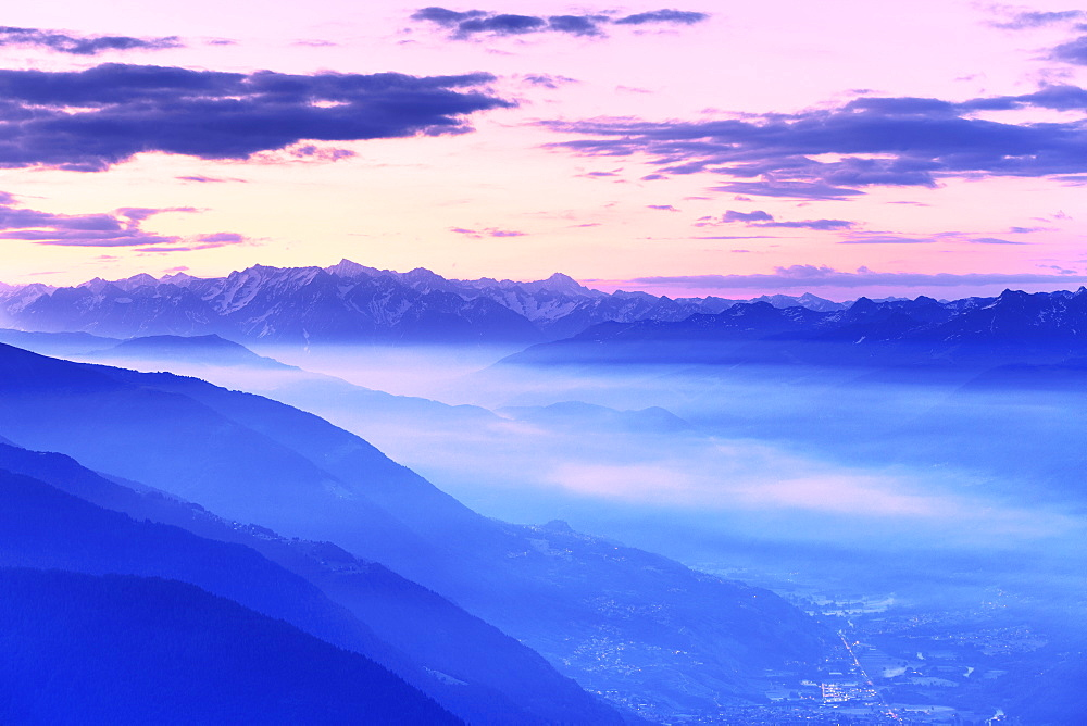 Fog in the valley during sunrise. Valtellina, Lombardy, Italy, Europe.