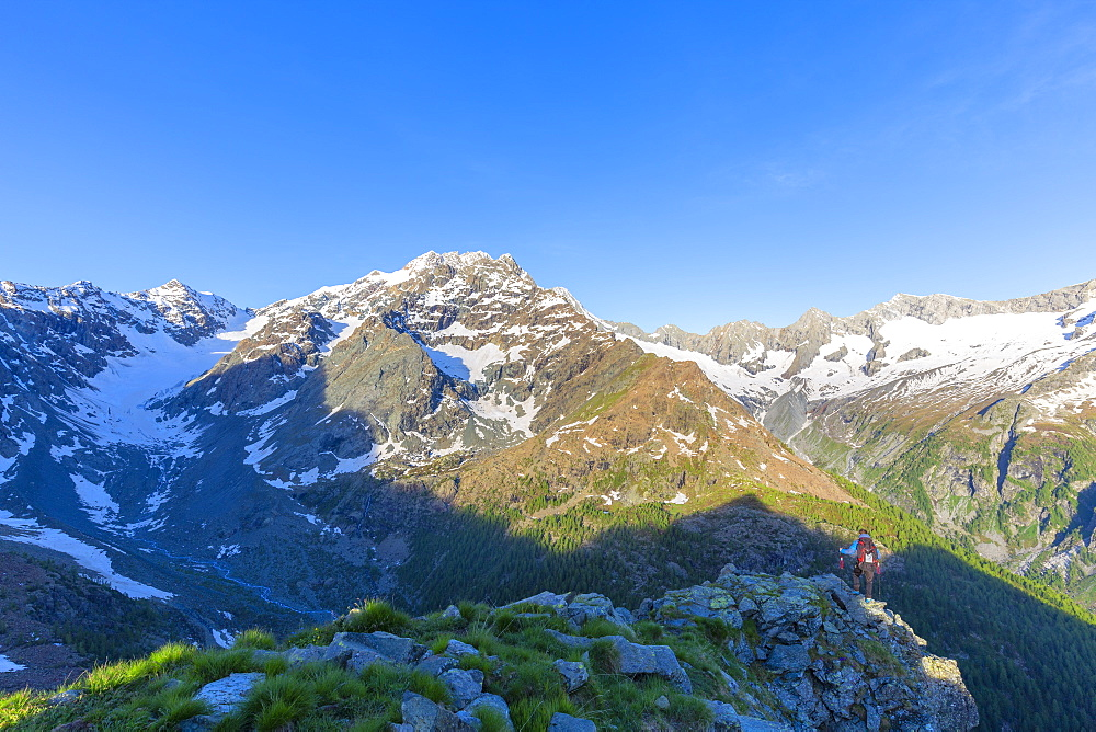 A hiker looks at Mount Disgrazia from above, Chiareggio valley, Valmalenco, Valtellina, Lombardy, Italy, Europe
