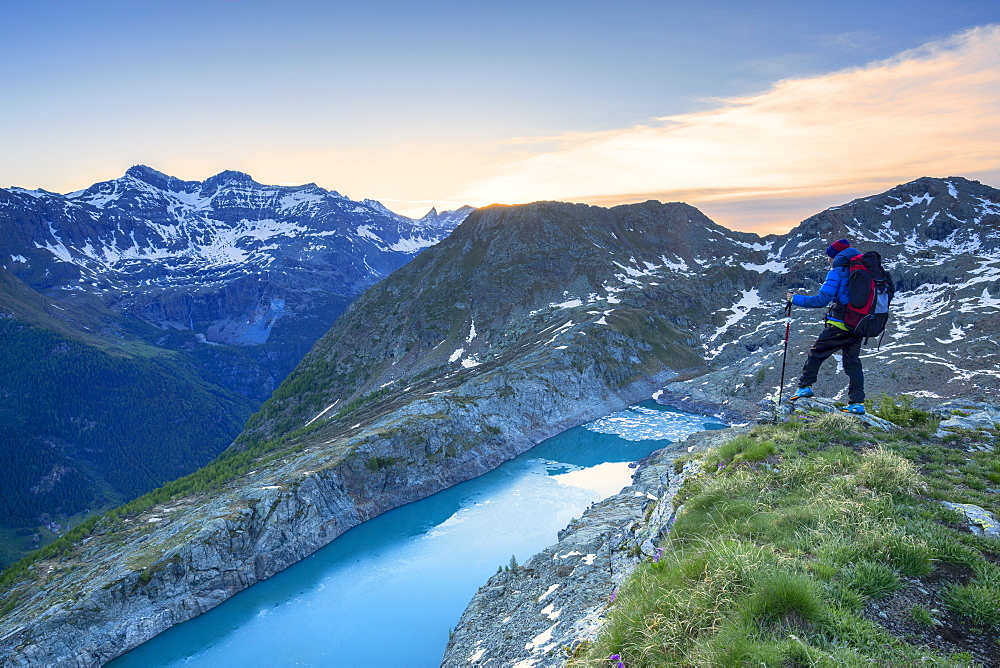 A hiker looks at Lake Pirola from above at sunrise, Chiareggio valley, Valmalenco, Valtellina, Lombardy, Italy, Europe