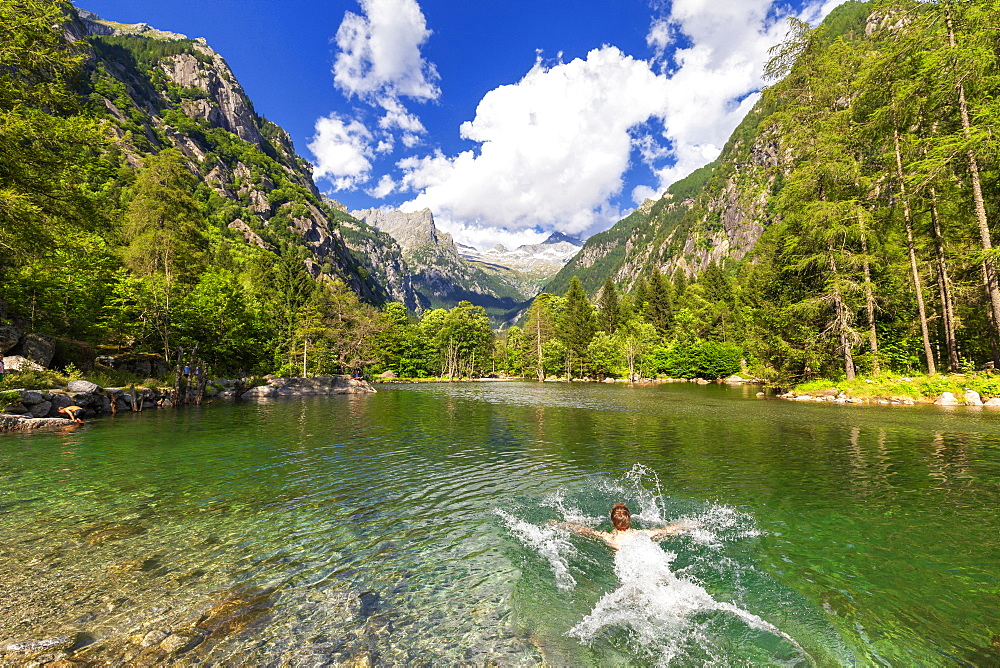 A boy swims in a clear alpine lake, Val di Mello (Mello Valley), Valmasino, Valtellina, Lombardy, Italy, Europe