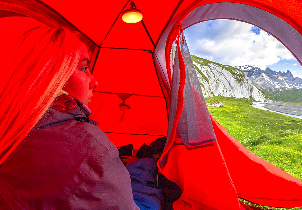 Young girls looks out of a red tent, Unterer Segnesboden, Flims, District of Imboden, Canton of Grisons (Graubunden), Switzerland, Europe - 1269-232