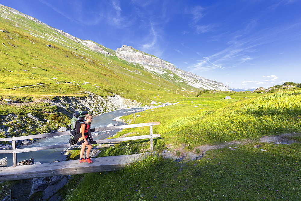 Woman hiker runs across a footbridge, Unterer Segnesboden, Flims, District of Imboden, Canton of Grisons (Graubunden), Switzerland, Europe - 1269-235