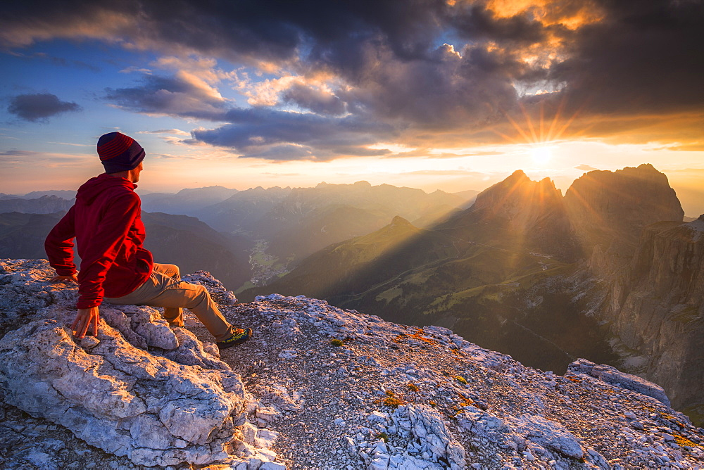 Hiker looks at sunset from Piz Pordoi, Fassa Valley, Trentino, Dolomites, Italy, Europe