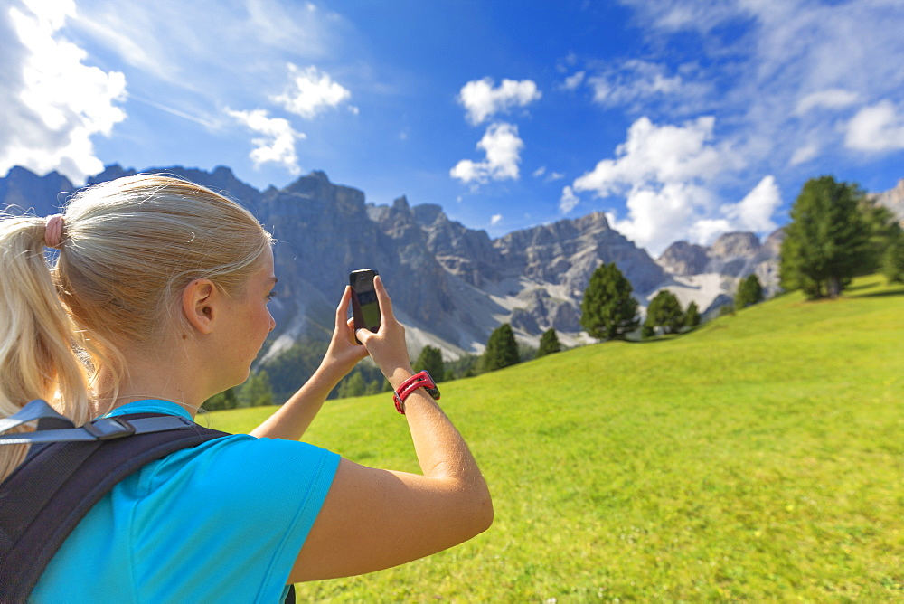 Girl take a photo with a smartphone. Longiarù, Badia Valley, South Tyrol, Dolomites, Italy, Europe. - 1269-291