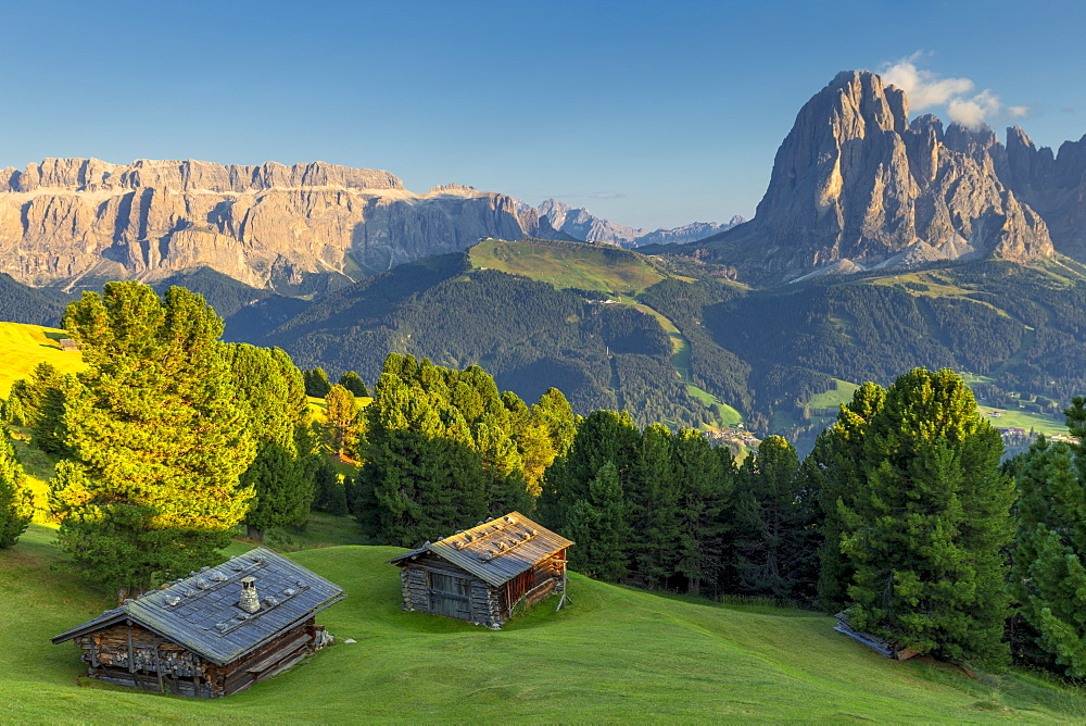 Last rays of sun on traditional huts with view on Sassolungo and Sella Group, Gardena Valley, South Tyrol, Dolomites, Italy, Europe