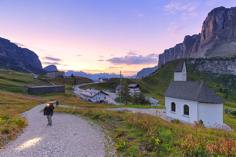 Hiker walks on a track during sunrise, Gardena Pass, Gardena Valley, South Tyrol, Dolomites, Italy, Europe