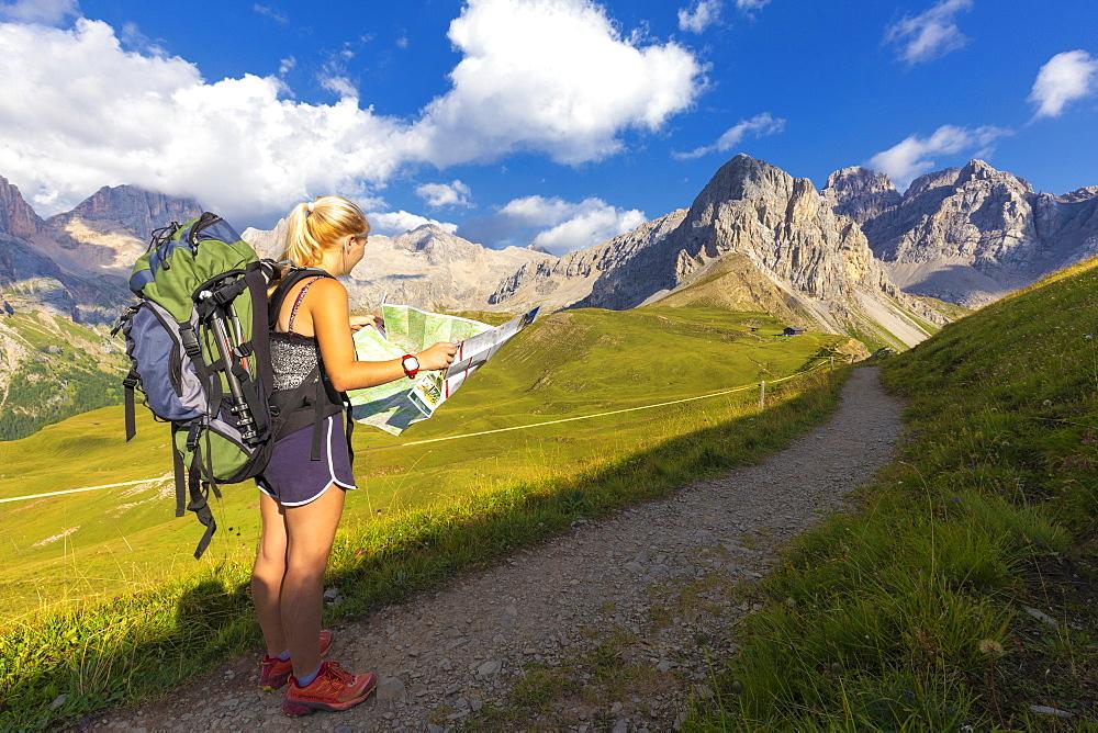Hiker reading map near San Nicolo Pass, Fassa Valley, Trentino, Dolomites, Italy, Europe