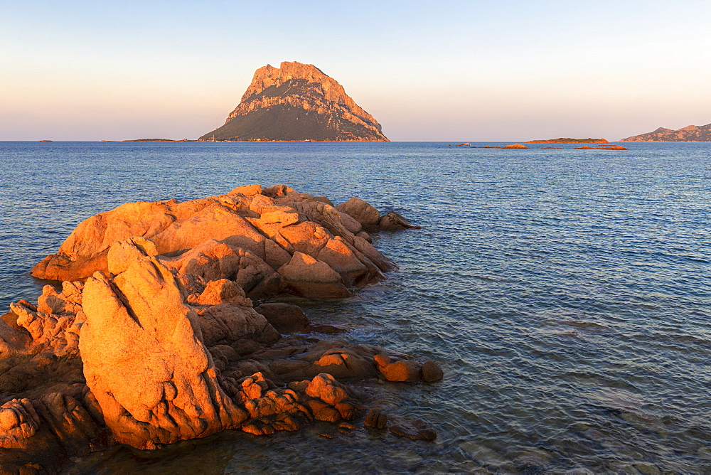 Sun illuminates rocks with Tavolara Island in the background at sunset, Loiri Porto San Paolo, Olbia Tempio province, Sardinia, Italy, Mediterranean, Europe
