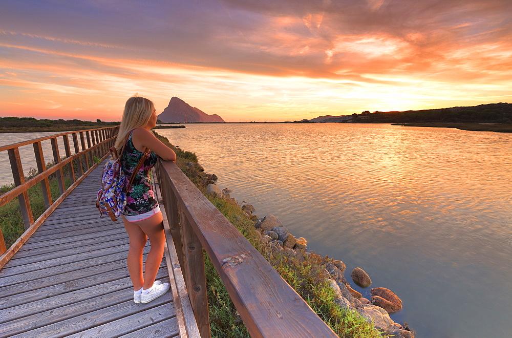 A girl looks sunrise from a walkway. Porto Taverna, Loiri Porto San Paolo, Olbia Tempio province, Sardinia, Italy, Europe. - 1269-344
