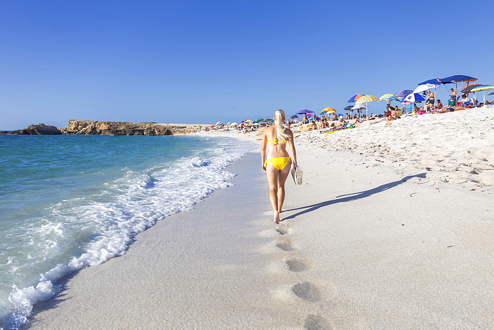 Young girl wit yellow swimsuit walks on the beach of Is Arutas, Cabras, Oristano province, Sardinia, Italy, Europe.