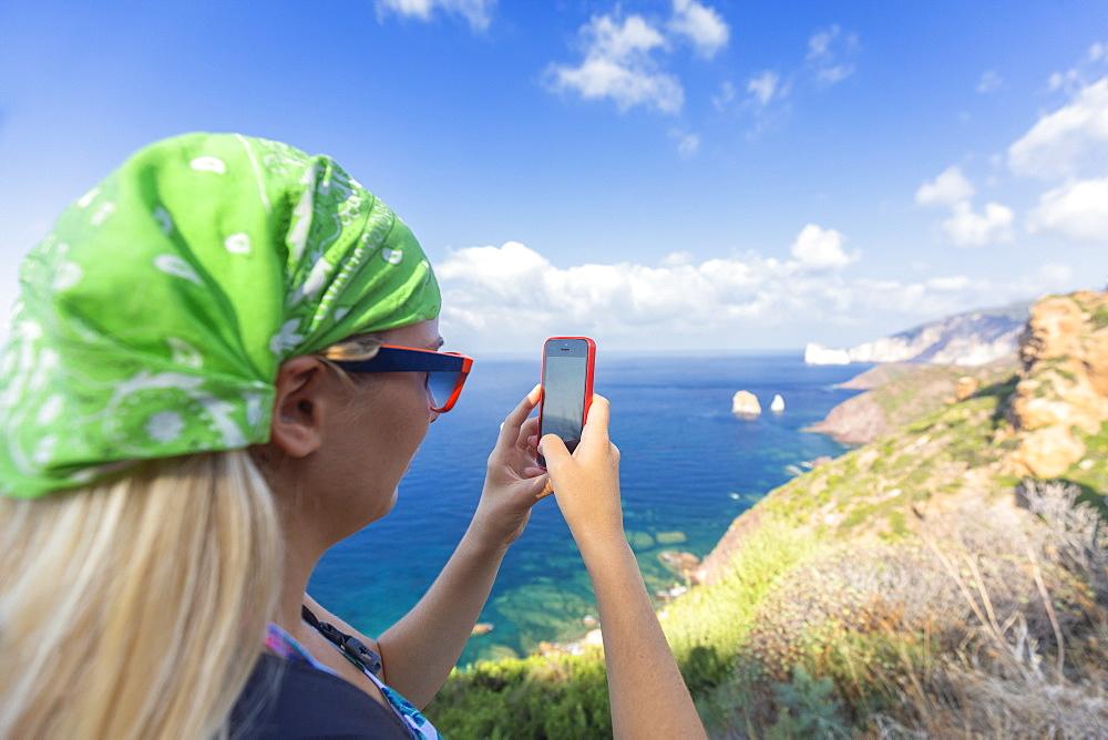 A tourist take a photo with smartphone. Nebida, Iglesias, Sud Sardegna province, Sardinia, Italy, Europe. - 1269-374