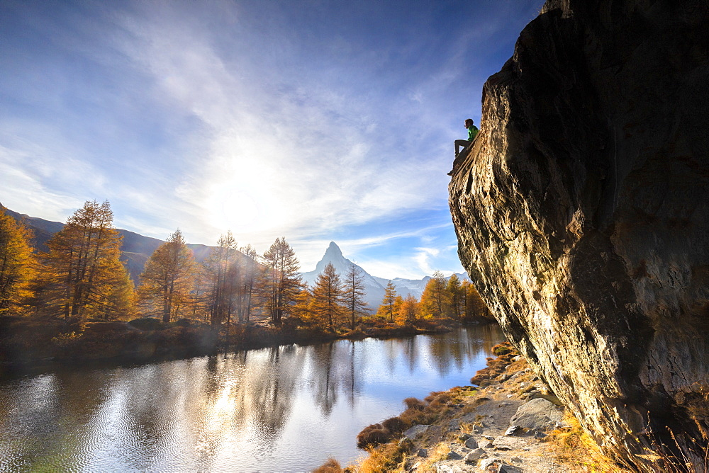 Man on rock above Grindjisee Lake during autumn in Zermatt, Switzerland, Europe