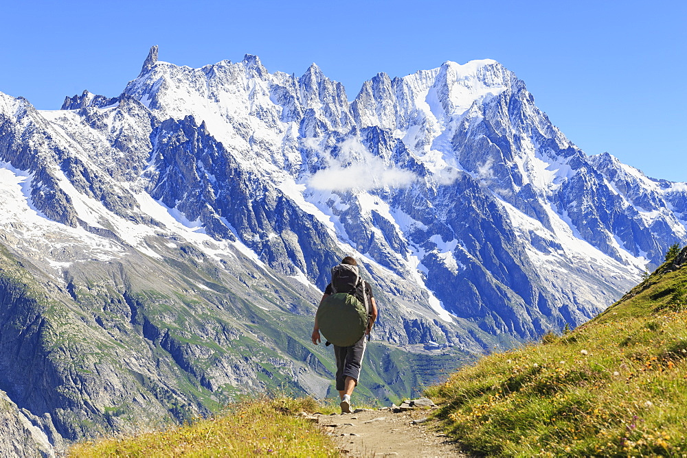 Hiker runs along trail with views on Grandes Jorasses and the Giant Tooth, Veny Valley, Courmayeur, Aosta Valley, Italy, Europe