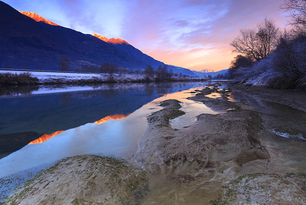 The colors of sunset are reflected in the Adda River, Valtellina, Lombardy, Italy, Europe - 1269-61