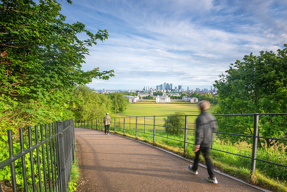 Tourist walking in Greenwich Park with Canary Wharf in the background, London, England, United Kingdom, Europe