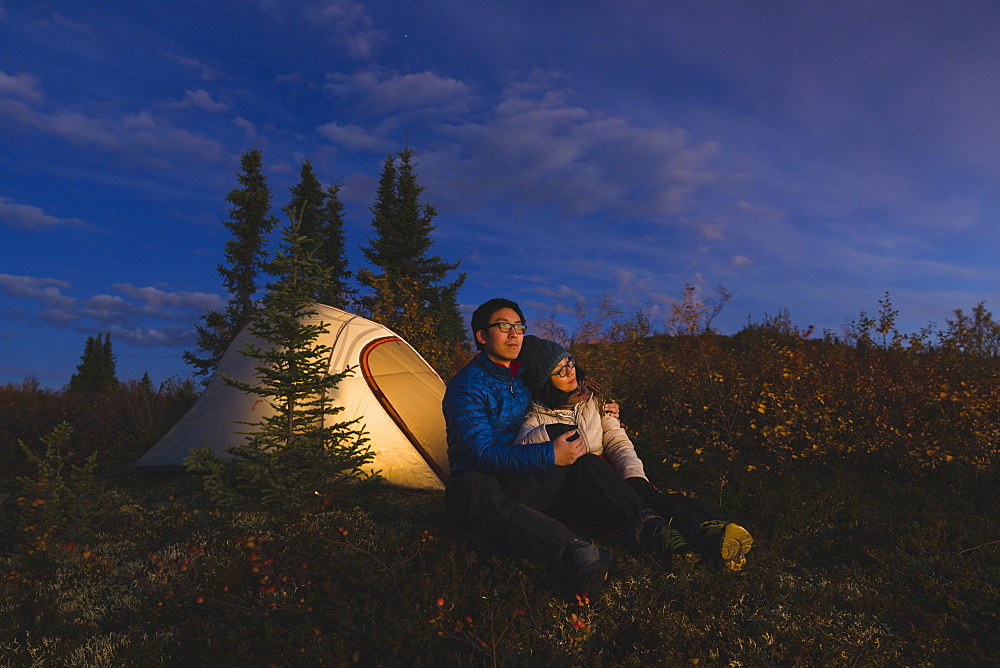Couple sitting in front of an illuminated tent, Alaska, United States of America, North America - 1275-2
