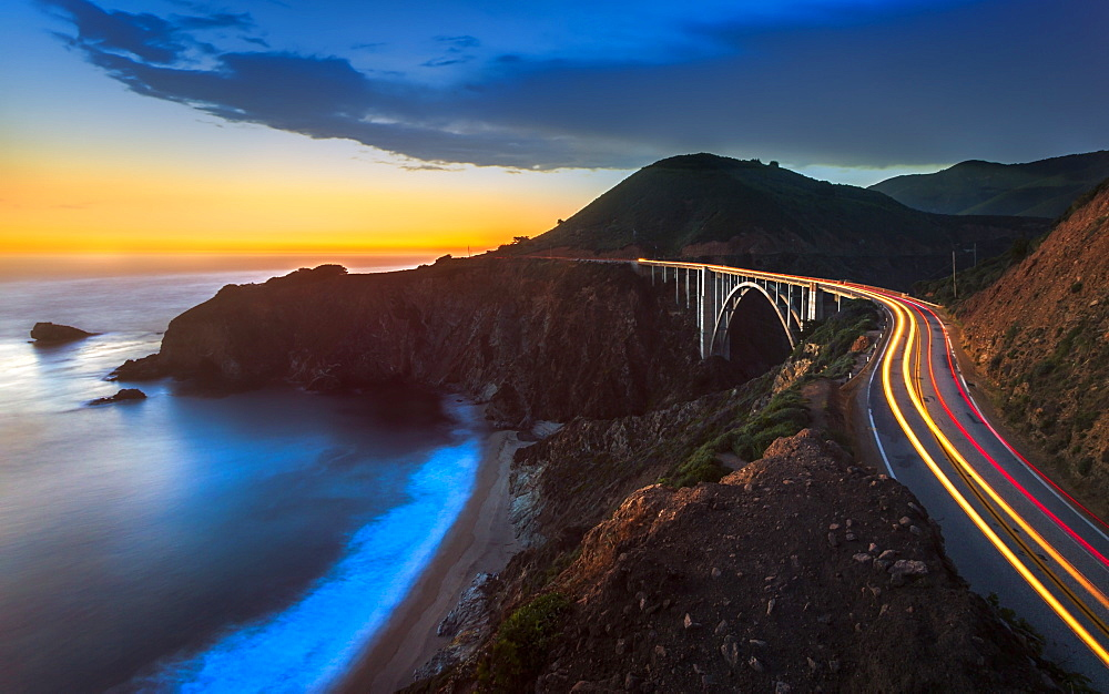 Sunset over Bixby Creek Bridge and car trail lights, Big Sur, California, United States of America, North America