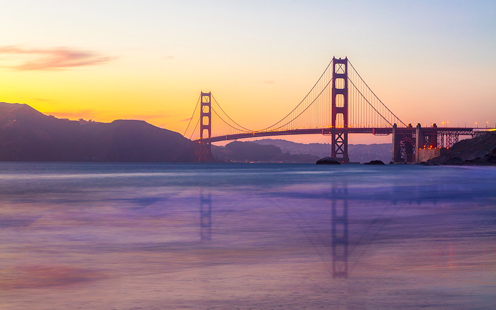 Soft flowing water reflects the beautiful Golden Gate Bridge at sunset, San Francisco, California, United States of America, North America
