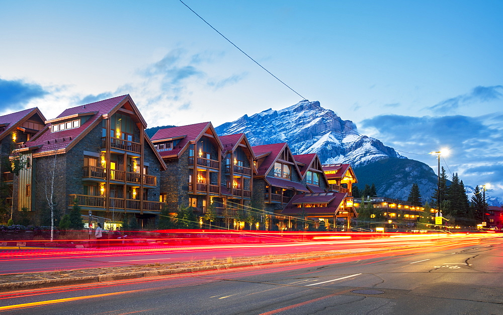 Trail lights on Banff Avenue and mountains in background at dusk, Banff, Banff National Park, Alberta, Canada, North America