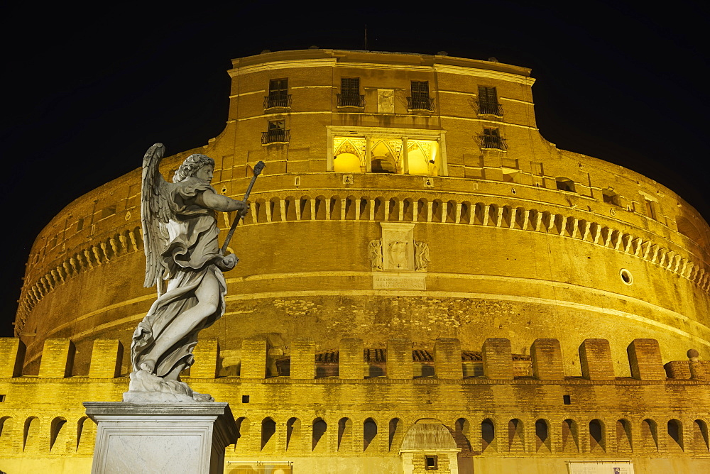 Rome Italy Castel Sant'Angelo facade at night with statue on Ponte Sant'Angelo.
